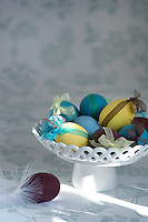 A white ceramic dish filled with coloured eggs tied with different coloured ribbon