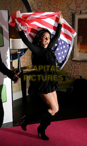 """KATIE PRICE (aka JORDAN).Photocall promoting ITV2 new series """"Katie and Peter Stateside"""", Soho Hotel, London, England..April 14th, 2009.full length black dress sheer sleeves  boots flag american stars striped mouth open arms in air gesture funny.CAP/FIN.©Steve Finn/Capital Pictures."""
