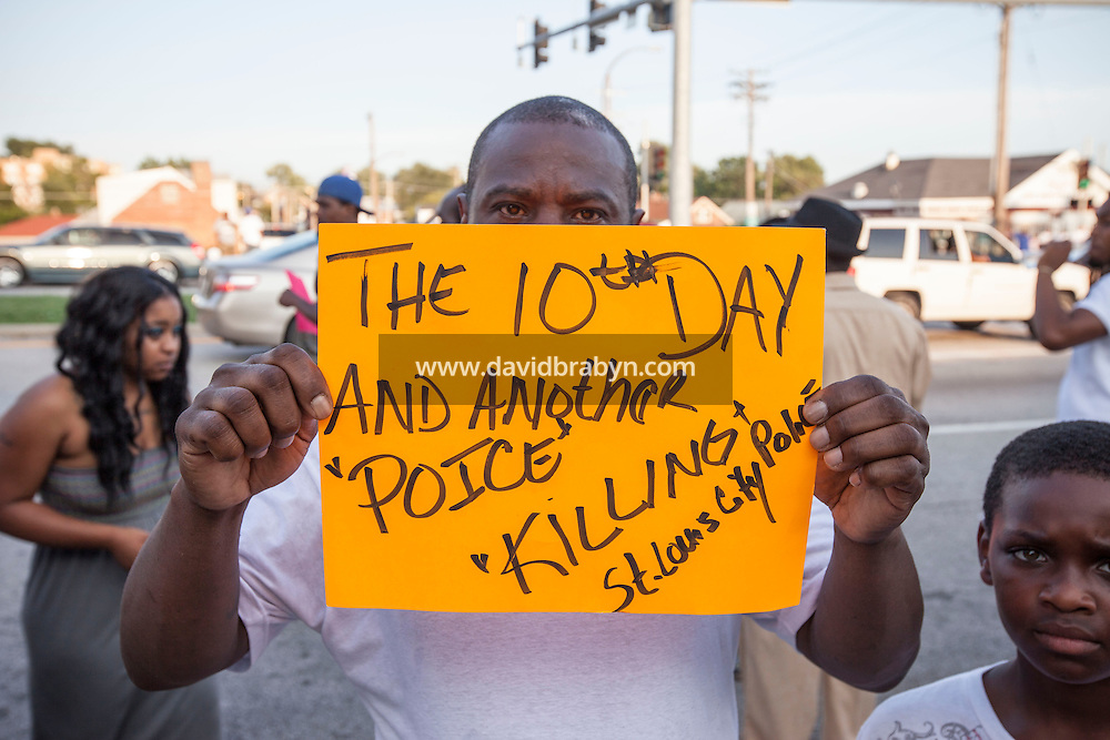 "HSUL 20140819 United States, St Louis, MO. Michael Conahamm holds up a sign denouncing ""Poice killings"" (sic), as he stands nearby to where St. Louis police say officers shot and killed a 23-year-old man who was wielding a knife and refused to drop it on August 19, 2014 in St Louis, Missouri. Photographer: David Brabyn"