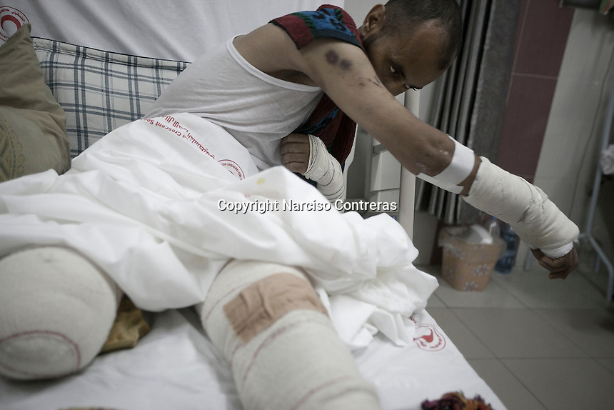 "In this Friday, Aug. 15, 2014 photo, Akran Ahmed Abdulatif, a 39 yo abulance paramedic, stretches on his bed as he recovers at Al-Quds hospital after he was severy injured as he attended an emergency call in Shujaya market where he additionally lost his right leg last 30 July during the ""Protective Edge"" Israeli military operation in Gaza Strip. (Photo/Narciso Contreras)"