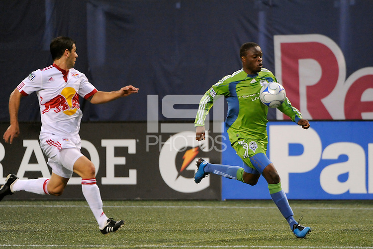 Steve Zakuani (11) of the Seattle Sounders is trailed by Carlos Mendes (4) of the New York Red Bulls. The New York Red Bulls  and the Seattle Sounders played to a 1-1 tie during a Major League Soccer match at Giants Stadium in East Rutherford, NJ, on June 20, 2009.