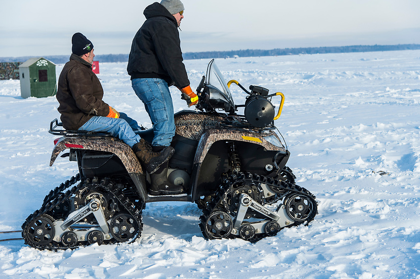 An ice fisherman moves his fishing shelter to a new spot on Little Bay de Noc using a tracked ORV four wheeler.