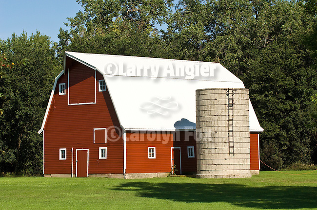 Red barn with white trim and roof, masonry silo and manicured lawn in Minnesota