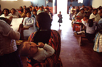 Child strapped to her back, a Bolivian Assembly of God devotee talks to fellow congregation women during a meeting in Quispe. Poor women throughout Latin America are the first attracted to the regimented life of home-grown Pentecostal religions.