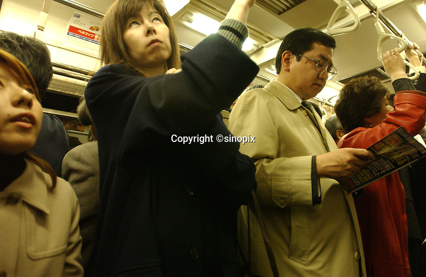 Businessmen and ladies stand in trains during the frantic and busy rush hour period in Tokyo.