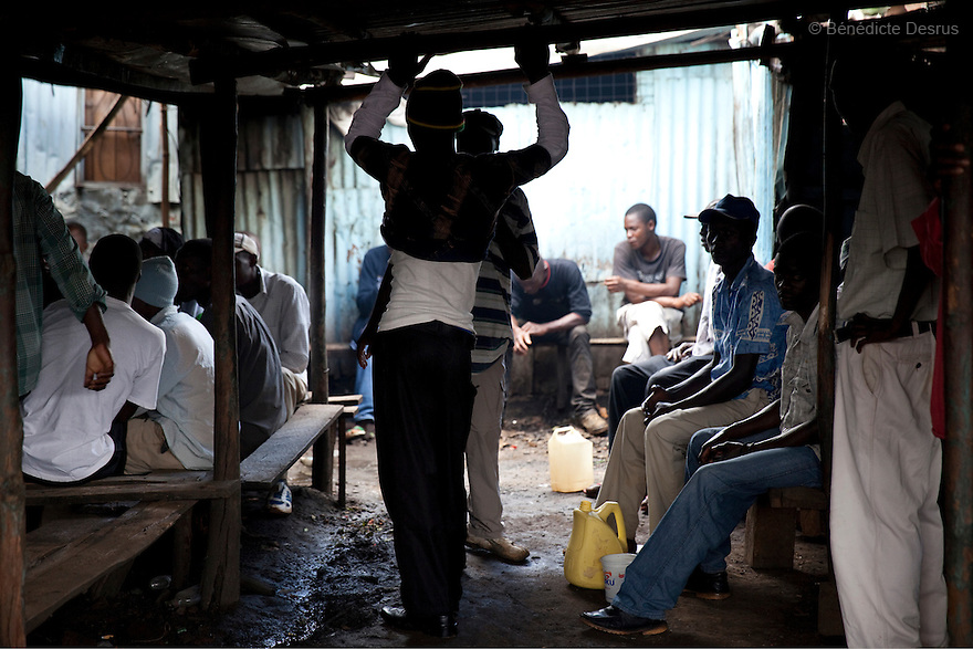 Kenyans drink Busaa, a traditional fermented beer, in a crowded Busaa club at midday in a Nairobi slum on April 7, 2013. Busaa is made by crudely fermenting maize, millet, sorghum or molasses. At Kshs 35 per liter it is much cheaper than a Kshs120 half-liter bottle of commercial beer. The local brew was legalised in 2010 and since then Busaa clubs have become increasingly popular in slums and rural areas. Drinking is on the rise in Kenya, especially among young people. Photo by Benedicte Desrus