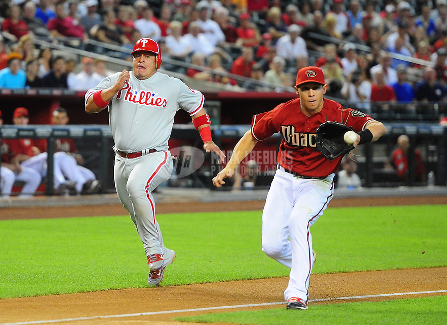 Apr. 25, 2012; Phoenix, AZ, USA; Philadelphia Phillies base runner Carlos Ruiz (left) is tagged out trying to score by Arizona Diamondbacks third baseman Cody Ransom in the second inning at Chase Field. Mandatory Credit: Mark J. Rebilas-USA TODAY Sports