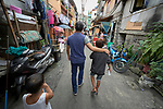 "Larren Jo ""LJ"" Bacilio, a teacher in the Alternative Learning System of the Kapatiran-Kaunlaran Foundation (KKFI), walks with one of his students in the Tondo neighborhood of Manila, Philippines. <br /> <br /> KKFI is supported by United Methodist Women."