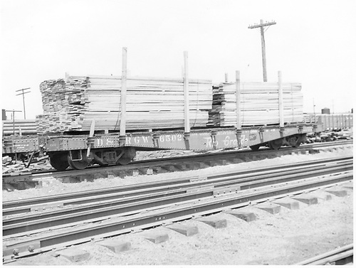 3/4 view of D&amp;RGW fishbelly flatcar #6502 loaded with lumber at Alamosa.<br /> D&amp;RGW  Alamosa, CO  Taken by Polkinghorn, R. S. - 1960