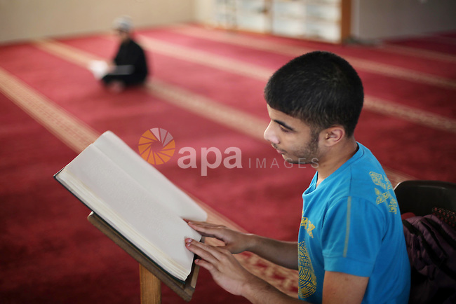 Palestinian blind youths read a copy of the Koran, Islam's holy book, at a religion school in Gaza City on June 21, 2016, during the Muslim fasting month of Ramadan. Photo by Mohammed Asad