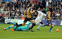 Bafetimbi Gomis of Swansea (18) is denied a goal by Petr Cech (on the ground) and Hector Bellerin (R) of Arsenal  during the Barclays Premier League match between Swansea City and Arsenal at the Liberty Stadium, Swansea on October 31st 2015