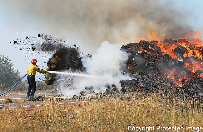 Bales of hay explode from a buring pile as a firefighter works to control a hay truck fire along I-82 at the Trall Road exit, Wednesday, Aug. 21, 2013. (Brian Myrick / Daily Record)