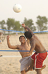 Sophy Teng, 21, left, tries to block a volleyball spike from his cousin Savin Chap, 24, during a warm summer evening at Holland State Park on Friday..(6/21/02)