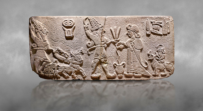 """Aslantepe Hittite Orthostat. Limestone, Aslantepe, Malatya, 1200-700 B.C. <br /> <br /> Scene of offering drink and sacrifice. The god, with a symbol of divinity above, is in the chariot while holding a boomerang in his hand and a sword at his waist. The same god holds a lightning bundle in the middle. On the right, the king offers a drink to god. The inscription above reads """"Great, powerful King Sulumeli"""". A servant stands behind holding a bull for sacrifice to the gods. Anatolian Civilisations Museum, Ankara, Turkey<br /> <br /> Against a grey art background."""