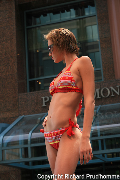Bikini Village swimsuit fashion show in Montreal, Canada, outdoor stage, model stops at end of runway to pose.
