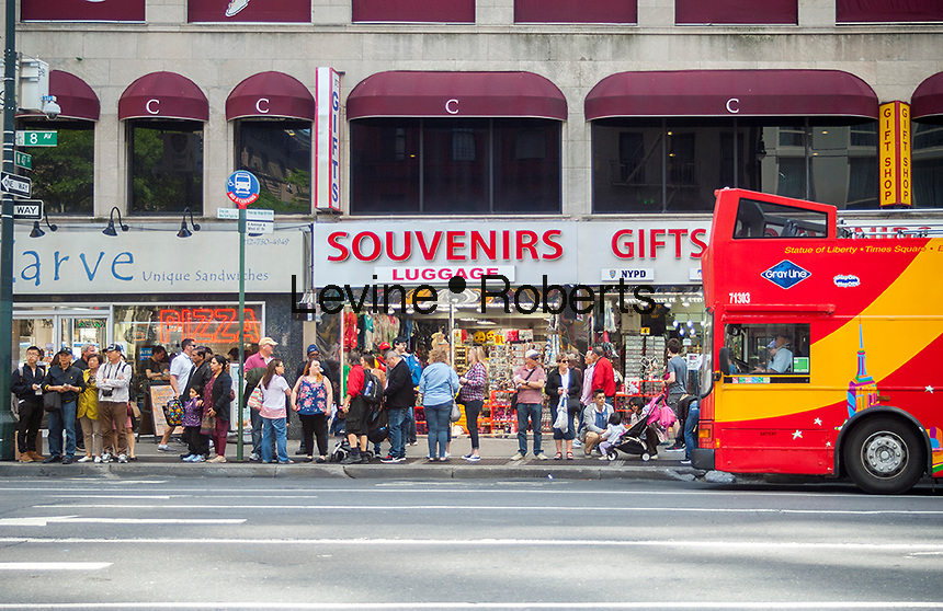Tourists line up in Midtown Manhattan in New York on Sunday, May 21, 2017 waiting for a tour bus. (© Richard B. Levine)