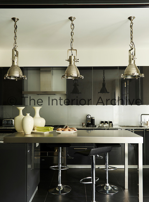 Pendant lights by Eichholtz hang above a steel island in a contemporary kitchen; the stools at the breakfast bar are by Lamboro. Black glossy cupboards at a touch of glamour.