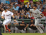 Boston Red Sox's Brock Holt, left, is run down and tagged out by Cleveland Indians third baseman Mike Aviles while trying to score from third during the first inning of a Major League Baseball game at Fenway Park in Boston on Tuesday, August 18, 2015. Photo by Christopher Evans