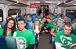 "MARCH 17, 2011 - LONG ISLAND NY: Dressed for St. Patrick's Day in green, young adults riding Long Island Railroad LIRR to Penn Station to celebrate in Manhattan, NY, USA, morining of St. Patrick's Day. At top of exit, words ""Penn Station"" appear in red on electric sign announcing next station stopping at.The LIRR added more than a dozen trains to Manhattan for St. Patrick's Day Parade. At rear, ads for (left) ING Direct and (right) New York Lottery. Train at Jamaica Station stop. For St. Patrick's Day safety, alcohol was forbidden in train cars, on platform and train station. EDITORIAL USE ONLY)"