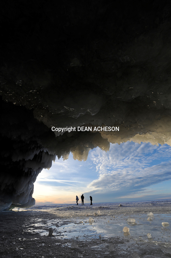 Hikers cross frozen Lake Superior in front of one of the ice caves along the Apostle Islands National Shoreline, Bayfield County, WI.