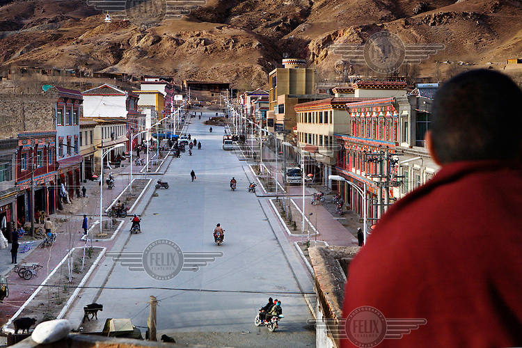 A monk stands atop the Dengke monastery looking up the main street which has recently received street lights and tarmac.