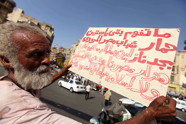 An Egyptian protester holds a placard against presidential candidate Ahmed Shafik during a protest at Cairo's Tahrir square, Egypt, 14 June 2012. Media reports on 14 June state that the Supreme Constitutional Court ruled that Ahmed Shafik could stand in the presidential election run-off, saying a law banning officials who served under Hosni Mubarak from running for office was unconstitutional. Photo by Majdi Fathi