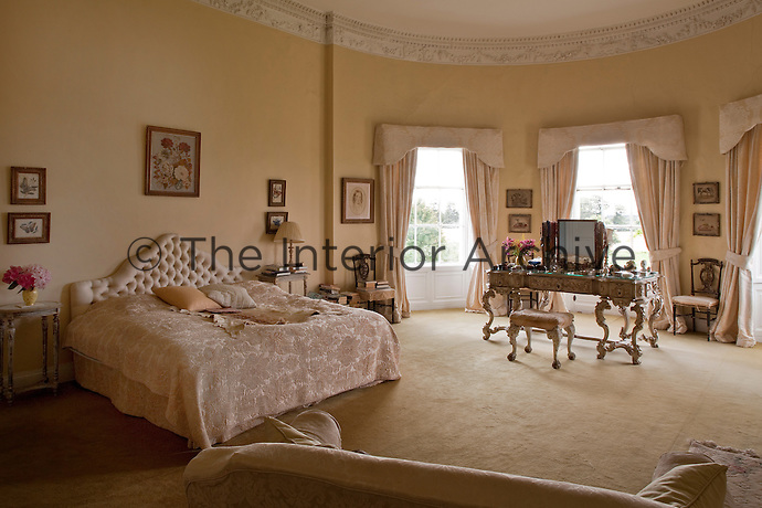 The decoration of the oval master bedroom is themed in various shades of peach and punctuated with three graceful windows