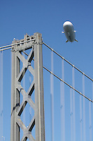 A Zeppelin NT operated by Airship Ventures passes over the West Tower of the Oakland-San Francisco Bay Bridge during its inaguaral voyage to San Francisco. The German manufactured airship differs from a blimp due to its rigid frame allowing for much larger aircraft.