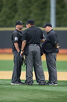 Umpires Matthew Hensel, Jessi Pereira, Andrew Glenn, and Frank Sylvester huddle to discuss a call during the ACC baseball game between the Georgia Tech Yellow Jackets and the Wake Forest Demon Deacons at David F. Couch Ballpark on March 26, 2017 in  Winston-Salem, North Carolina.  The Demon Deacons defeated the Yellow Jackets 8-4.  (Brian Westerholt/Four Seam Images)