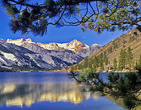 Twin Lakes with cabin and snow covered Eastern Sierra Mountains reflection and moon. California