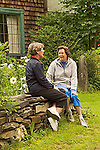 Two  senior Caucasian women in casual clothing sit and talk together on stone wall in country garden in Vermont, USA
