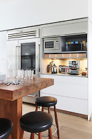 A sliding metal shutter reveals a countertop with numerous pieces of kitchen equipment