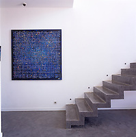 A detail of a concrete staircase against a white wall. A painting by Pierre Luc Poujol hangs on the wall.