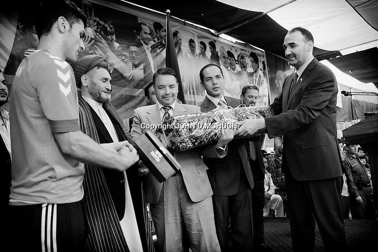 Atta Mohammad Noor (right), the governor of Balkh province, hands out gifts to the Afghan National Soccer Team after an official reception in Mazar-e Sharif 24 September 2013. Known as the King in the North, Atta is