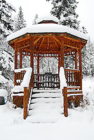 Snow covered gazebo with snow still falling.