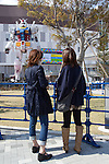 April 18, 2012, Tokyo, Japan - Two Japanese women stand in front of the 18-meter high full-scale model of the popular Gundam robot from the Japanese anime series created by Sunrise studios, which is on display in front of Diver City Tokyo Plaza, a new shopping mall in Odaiba opening on April 19.