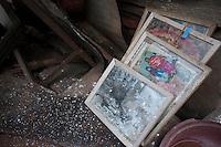 Frames of photographs lay on the rubble. Shanku, near Kathmandu, Nepal. May 9, 2015