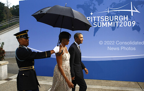Pittsburgh, PA - September 24, 2009 -- United States President Barack Obama (R) and first lady Michelle Obama arrive to the welcoming dinner for G-20 leaders at the Phipps Conservatory on September 24, 2009 in Pittsburgh, Pennsylvania. Heads of state from the world's leading economic powers arrived today for the two-day G-20 summit held at the David L. Lawrence Convention Center aimed at promoting economic growth. .Credit: Win McNamee / Pool via CNP