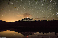 A mountaineer sets off fire works from the summit of Mt Rainier at midnight and its reflection in Reflection Lake.