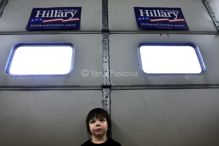 "Three-year-old Shawn Graham, from Kahoka, Missouri, watches U.S. Presidential Hopeful Sen. Hillary Clinton (D-NY) campaign at the Donnellson Fire Department on December 18, 2007, in Donnellson, Iowa. Clinton is beginning her ""Every County Counts"" tour in Iowa in preparation for the January 3 caucus in the state. Photo by: Yana Paskova for The New York Times.."