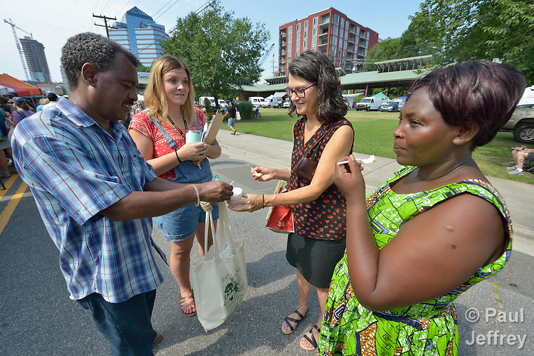 Two staff people from Church World Service help resettled refugees from Rwanda to taste peach ice cream for the first time in the Durham Farmers' Market in Durham, North Carolina. Church World Service resettles refugees in North Carolina and throughout the United States.<br /> <br /> Photo by Paul Jeffrey for Church World Service.