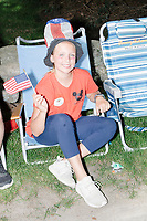 A girl holds an American flag and wears a red, white, and blue top hat while watching the 4th of July Parade in Amherst, New Hampshire, on Thu., July 4, 2019.