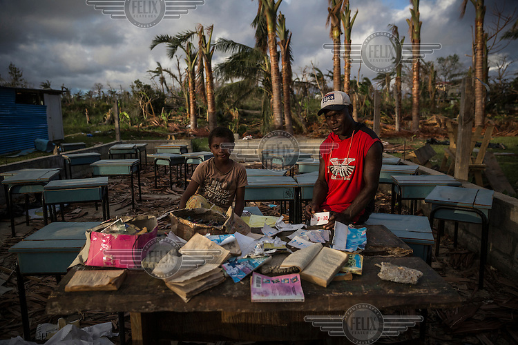 10 year old James with his school teacher Kenny Jonah (38) beside the few rescued items all that remains of his school in Etas village. It was destroyed by Cyclone Pam on 13 March 2015. He says: 'I was in a community shelter with my parents. When the strong wind came it was very noisy, I was afraid. Then my sisters and I fell asleep. Next morning we came to our house and it was destroyed. My school was destroyed too. Now I sleep with my parents in a tent and can't attend classes'.