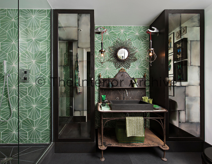 In the bathroom, a bold colour approach of black and shades of grey is offset with the single colour – viridian. The room is furnished in a mix of styles, with a hand basin set on a rustic style metal stand contrasting with a modern tiled shower cubicle. A pair of built-in cupboards with mirror doors gives the room a sense of space.