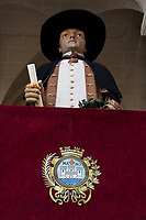 "Spain. Balearic Islands. Minorca (Menorca). Mahon. City Hall. A Giant statue which is used for the parade during the ""Festes de la Mare de Déu de Gràcia"", a traditional summer festival. The coat of arms of Mahon on a grant fabric. Maó (in Catalan) and Mahón (in Spanish), written in English as Mahon, is a municipality, the capital city of the island of Menorca, and seat of the Island Council of Menorca. The city is located on the eastern coast of the island, which is part of the autonomous community of the Balearic. In Spain, an autonomous community is a first-level political and administrative division, created in accordance with the Spanish constitution of 1978, with the aim of guaranteeing limited autonomy of the nationalities and regions that make up Spain. 7.09.2019 © 2019 Didier Ruef"