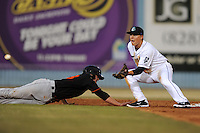 Asheville Tourists shortstop Pat Valaika #16 fields the pickoff attempt as Chance Sisco #23 slides in safely during a game against the Delmarva Shorebirds at McCormick Field on April 4, 2014 in Asheville, North Carolina. The Shorebirds defeated the Tourists 7-2. (Tony Farlow/Four Seam Images)