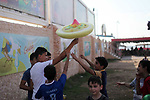 Palestinian children carry candy cotton as they play at a park in Gaza city on August 18, 2019. Fayiz al-Wakeel, or 'the smile maker', developed his own candy floss machin to work by battery power to help him moving between vital districts in the Gaza city and make cotton candy with lovely shapes.. Photo by Mahmoud Ajjour