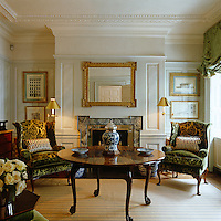 A pair of wing-backed armchairs upholstered in dark green damask flank the fireplace in the morning room