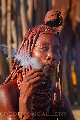 A Himba woman with a traditional leather headress and ochre covered hair braids smoking her pipe. Himba women cover their bodies with a traditional mixture of ochre and butter fat giving their skin and hair a reddish coloration. Himba are nomadic herders of goats and cattle, living in the dry desert regions of northwestern Namibia and southern Angola.
