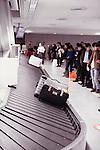 People waiting for their luggage at Narita International airport baggage claim conveyor carousel, Japan